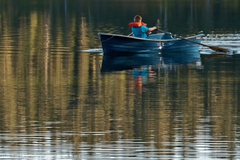 A boy rows a rowboat across Takhlakh Lake
